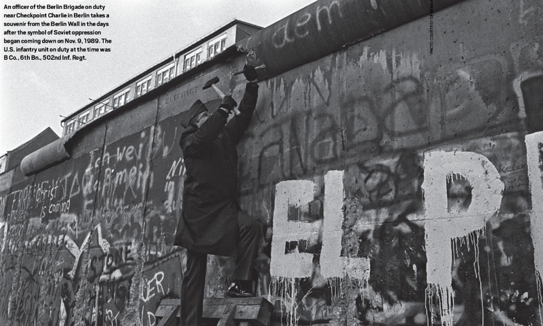 An Berlin Brigade officer near Checkpoint Charlie in Berlin takes a souvenir from the Berlin Wall