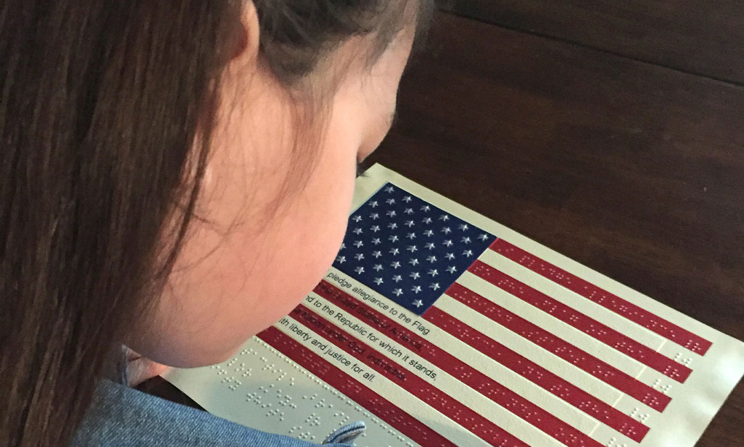 A child explores a Braille version of the U.S. flag