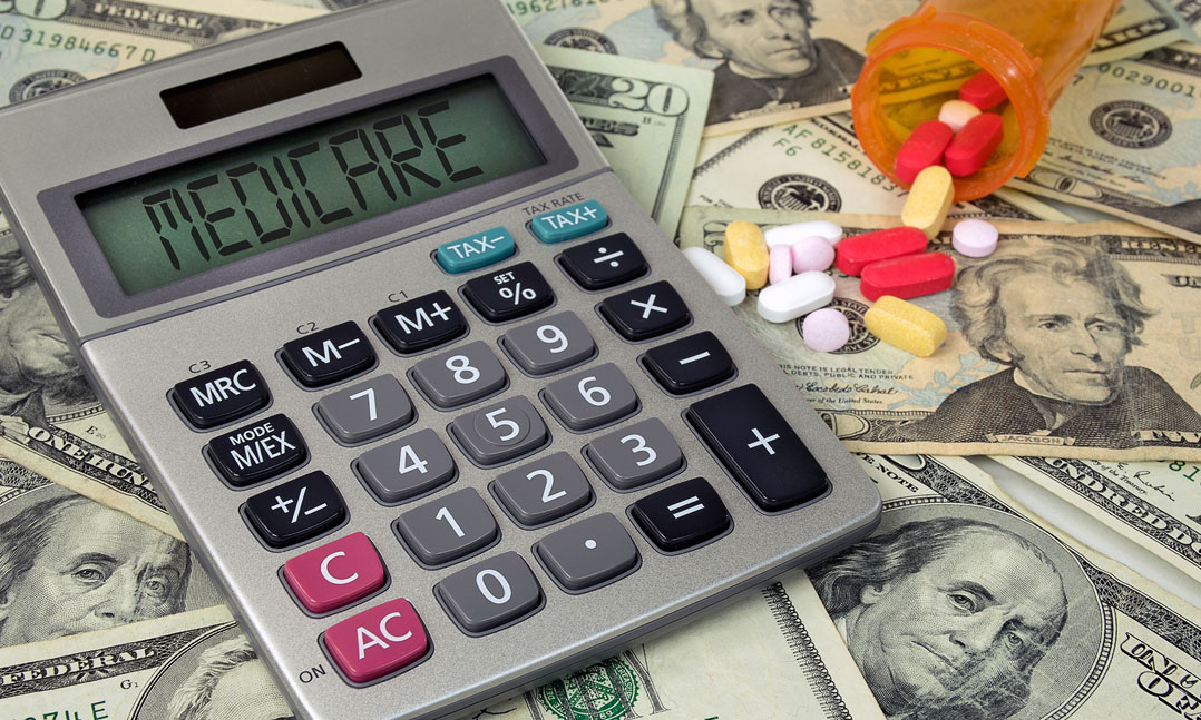 Calculator displaying Medicare and pills from a spilled prescription bottle sit on top of money