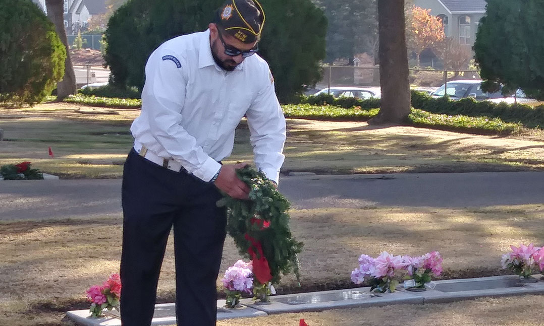 A VFW member prepares a wreath for a veteran's grave during Wreaths Across America