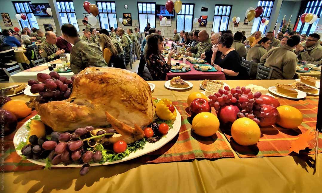 A Thanksgiving turkey sits on a table as service members enjoy a Thanksgiving meal together at Fort Irwin