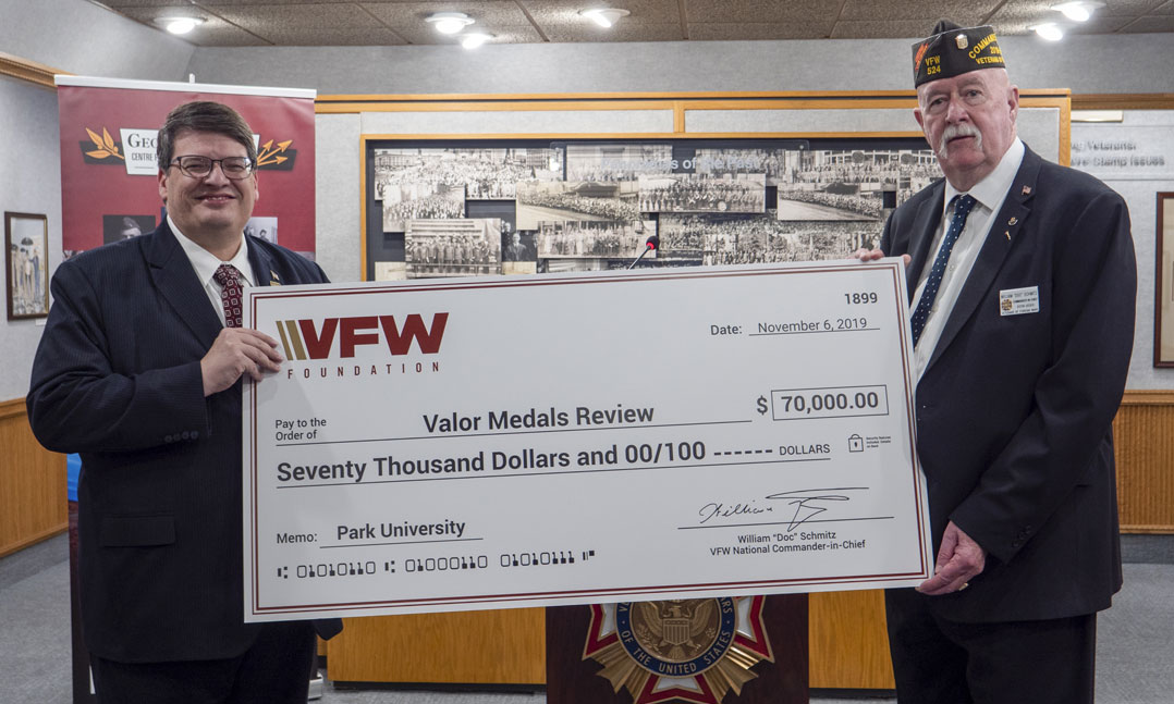 Park University President Dr. Greg Gunderson left accepts a donation from VFW National Commander William Doc Schmitz