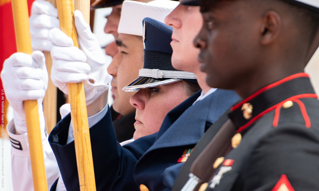 Men and women of a joint color guard stand at attention