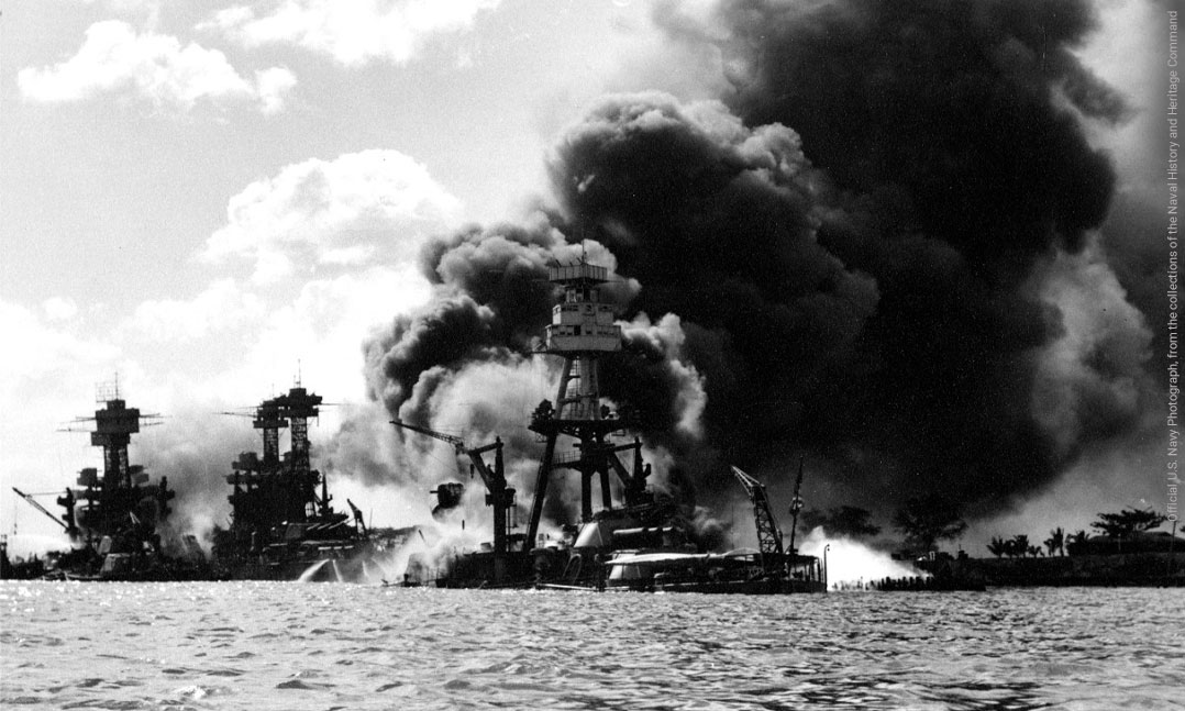 View looking up Battleship Row on 7 December 1941, after the Japanese attack with USS Arizona in the center, burning furiously