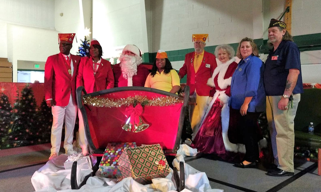Men and women of the VFW, VFW Auxiliary and the Military Order of the Cootie present children with Christmas gifts