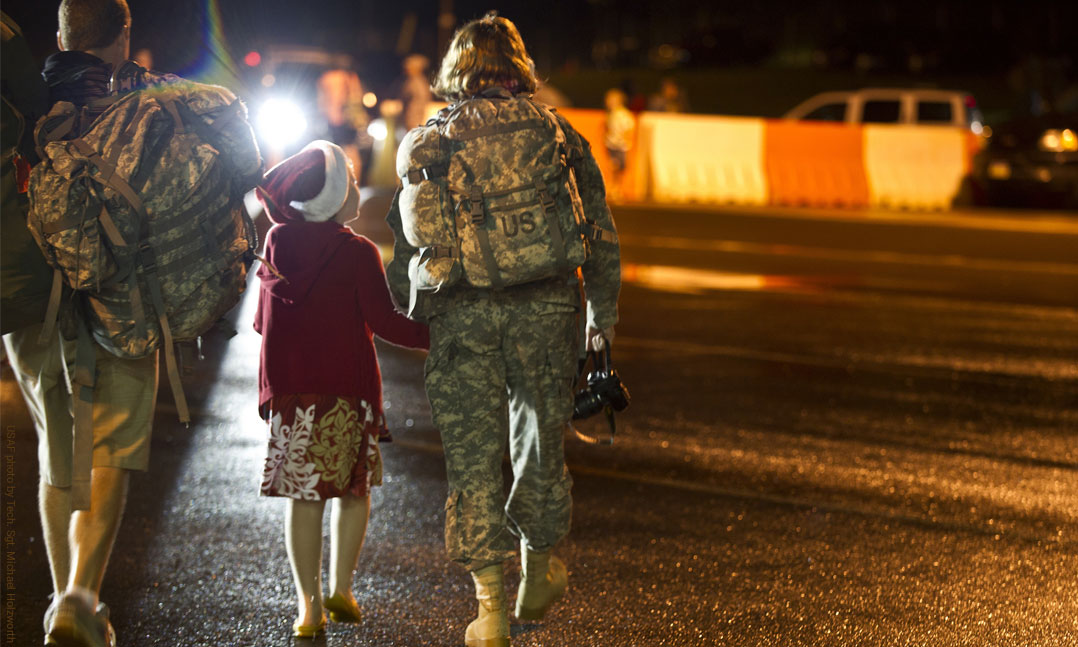 Man carries his wife's bags while young girl gets reacquainted with her mom who returned from Iraq deployment
