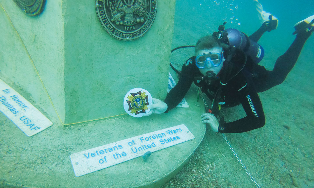 VFW Junior Vice Commander dives to place a VFW marker at the first underwater veterans memorial in Dunedin Florida