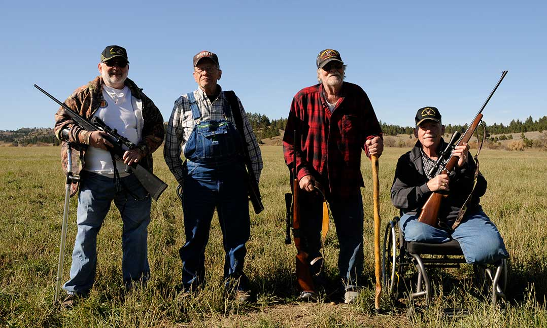 Four decorated Purple Heart veterans stand in a field with firearms while attending a special hunt on the Great Planes