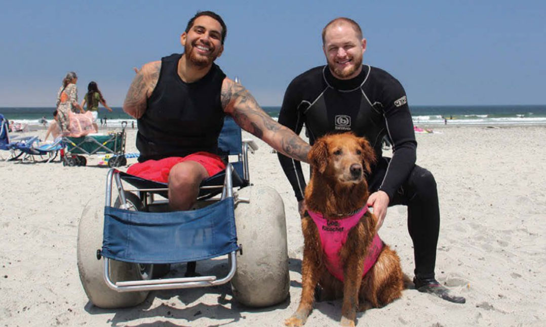 Two wounded warriors enjoy the beach with therapy dog Ricochet