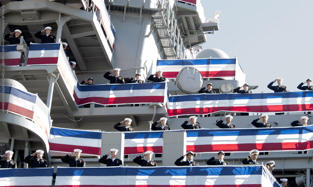 Sailors aboard a U.S. naval ship saluting