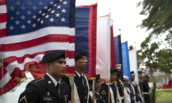 A joint color guard stands in front of flags