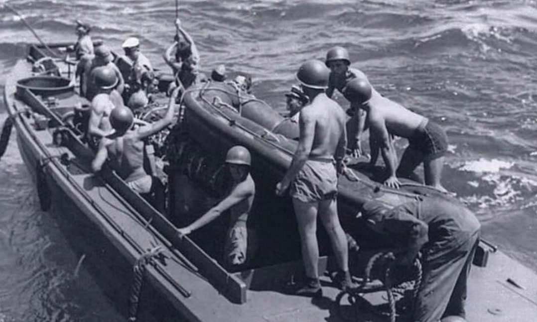 a landing craft personnel ramped carries frogmen and a seven-man IBS to their drop-off point during world War II