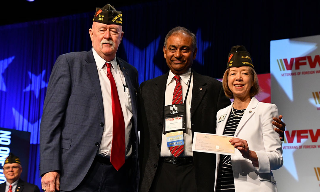 VFW National Commander Doc Schmitz, left, and VFW Quartermaster General Debra Anderson, right, accept a $100,000 check from Prasad Reddy with Twisted X in support of VFW youth programs