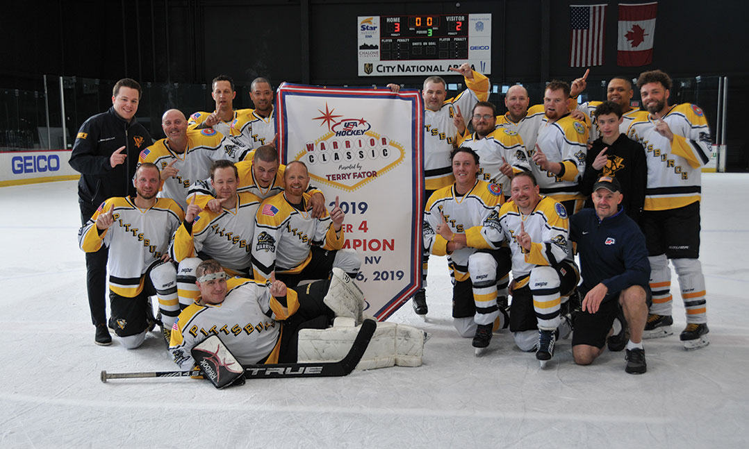 Members of the Pittsburgh Warriors wounded veterans hockey team pose on the ice after winning the 2019 Tier IV Warrior Classic title game
