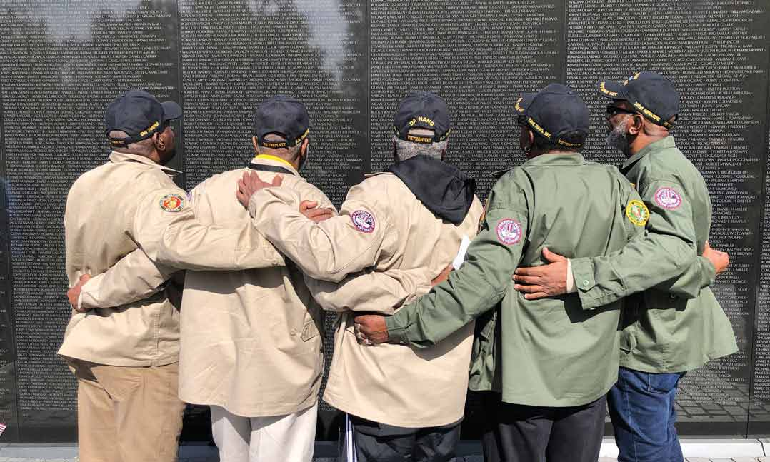 Five brothers who all served in Vietnam embrace in front of the Vietnam Veterans Memorial at the National Mall
