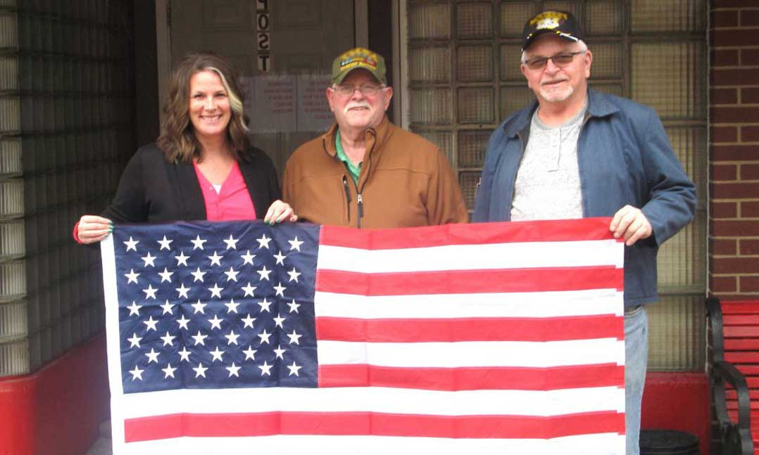Two men and a woman hold a U.S. flag donated by the local VFW