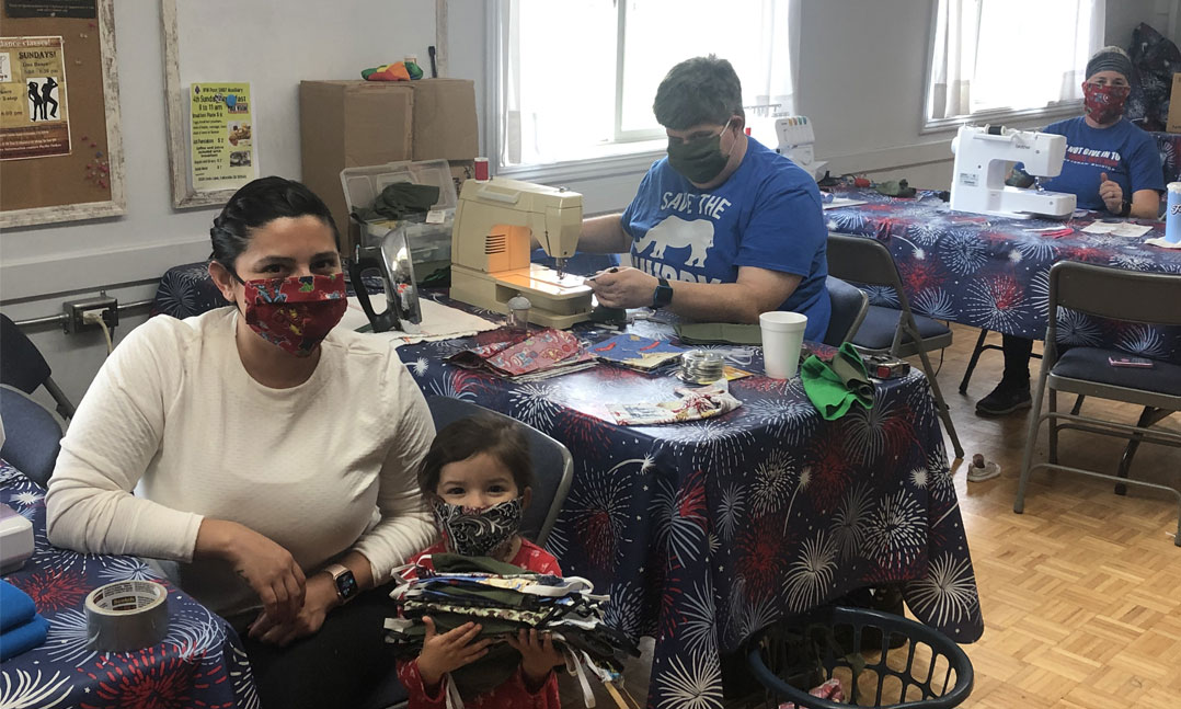 Members of a VFW Post make masks for active duty sailors