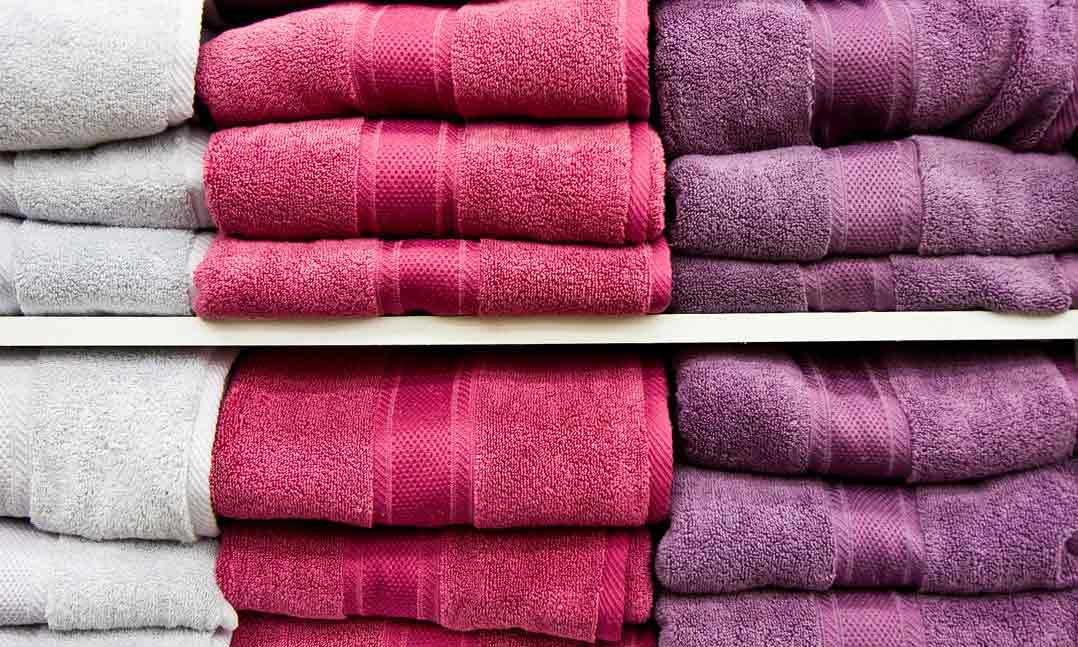 Stacks of white, pink and purple bath towels