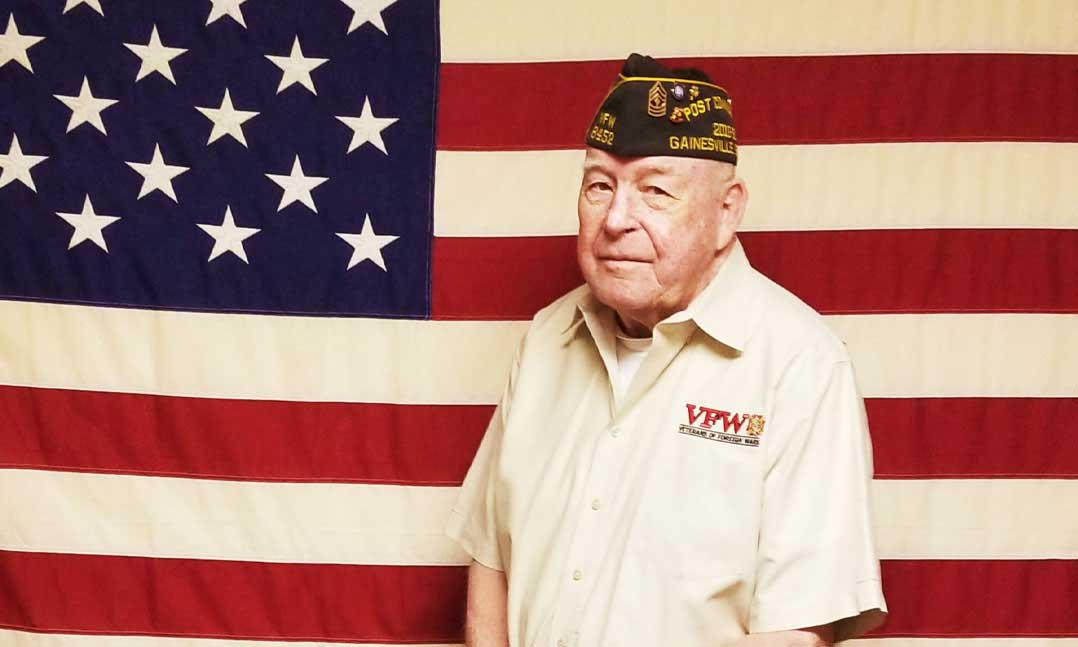 VFW member standing in front of the flag