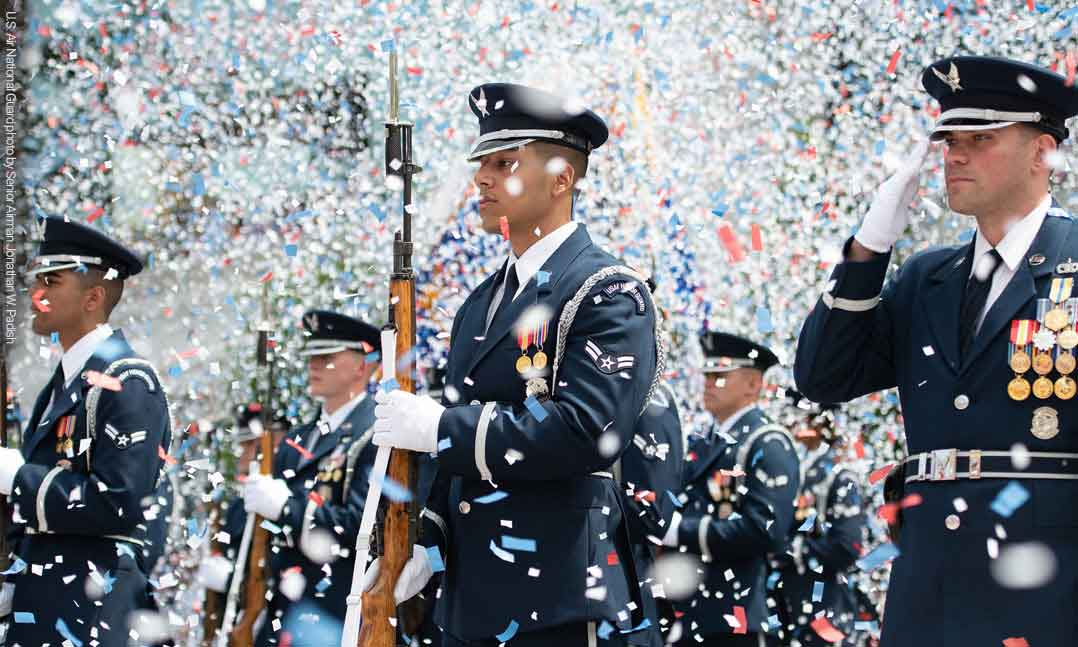 Confetti flies around members of the US Air Force in their dress blue uniforms