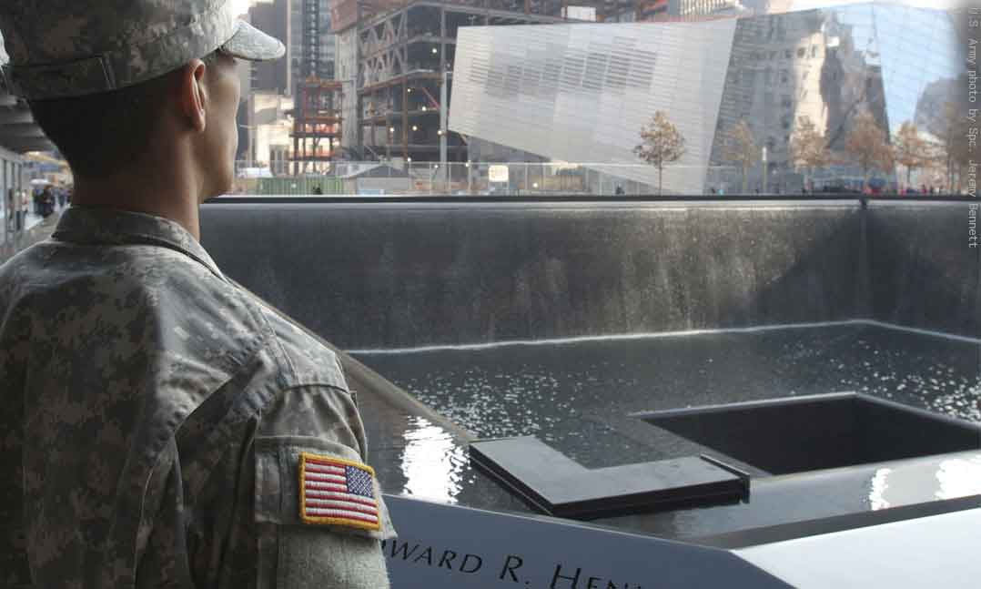 Soldier in uniform stands in front of the World Trade Center Memorial