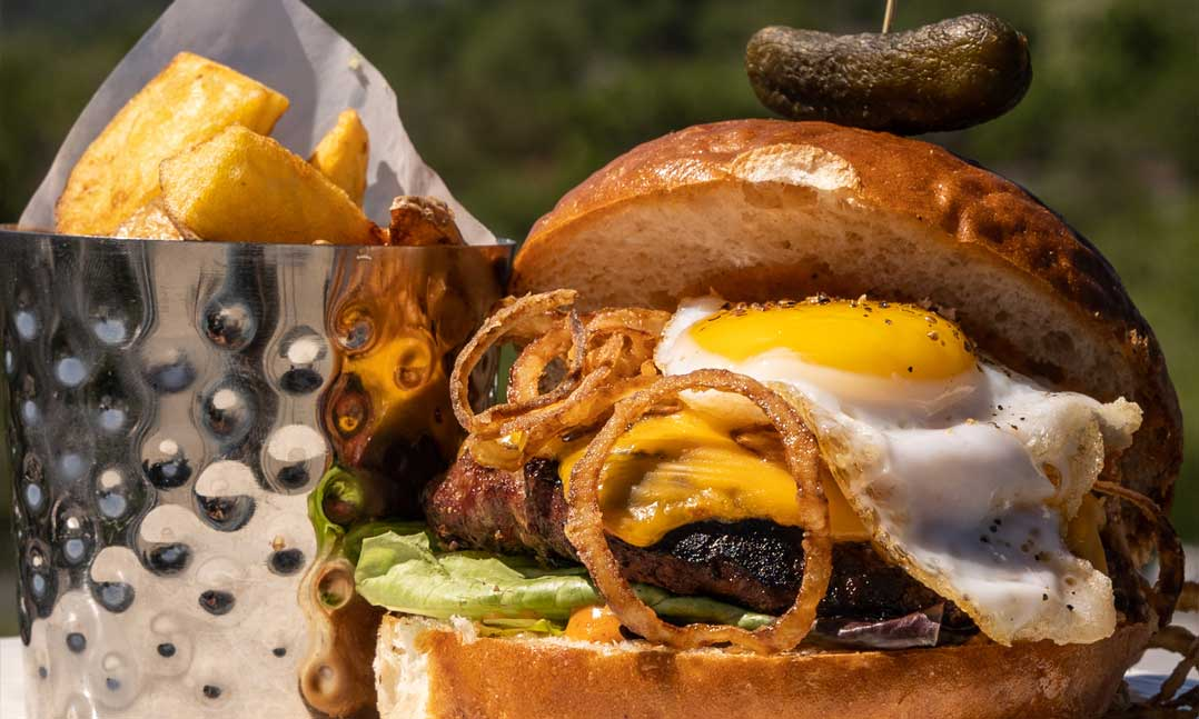 cheeseburger with fried onions and egg with french fries