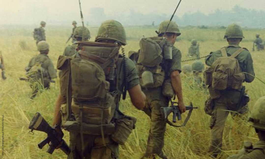Soldiers walking through a field during the Vietnam War