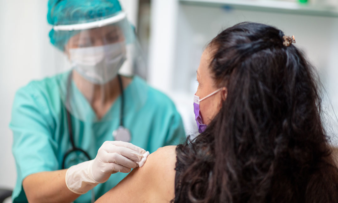 Nurse wearing PPE gives a woman a flu shot